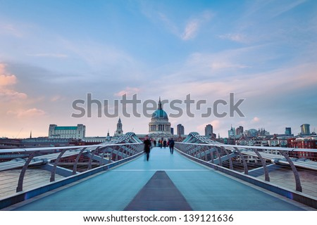 People walking over Millennium bridge at dusk. St Pauls cathedral in the background.