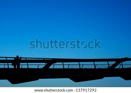 People walking over Millennium bridge in London, UK. - stock photo