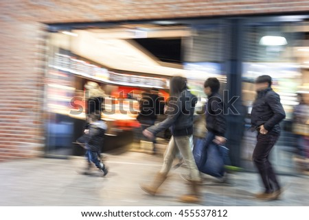 People walking past a store window, motion blur