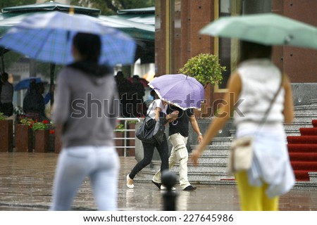 People walking with umbrellas in the rain - stock photo