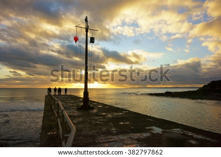 People watching a dramatic sunset over Porthleven Pier with an incoming tide and surfers in the sea, Cornwall, England, UK  - stock photo