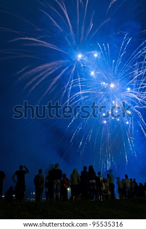 People watching beautiful blue fireworks - stock photo