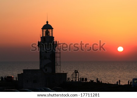 people watching the sunset near an ancient lighthouse during the sunset - stock photo