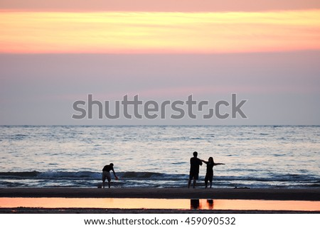 people watching the sunset on the beach