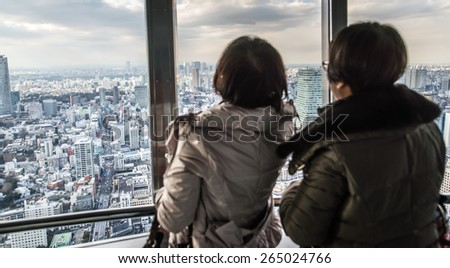 people watching tokyo skyline from view tower. concept about travel, asian metropolis, and people - stock photo