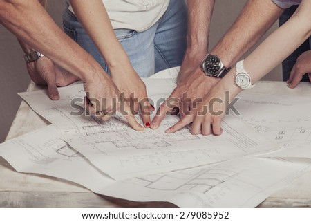 People who work with drawings on the table in the white room - stock photo