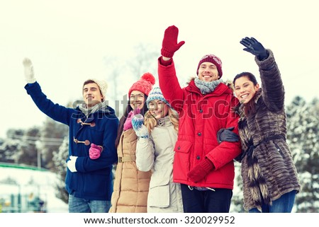 people, winter, friendship, sport and leisure concept - happy friends waving hands on ice rink outdoors