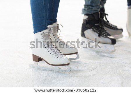 people, winter sport and leisure concept - close up of legs in skates on skating rink - stock photo