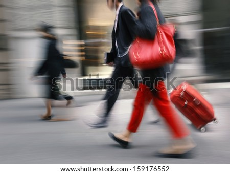 People with a red bag and a suitcase walking down the street. Intentional motion blur