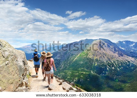 People With Backpacks Hiking On Summer Vacation In Mountains Father His Family Enjoying Time