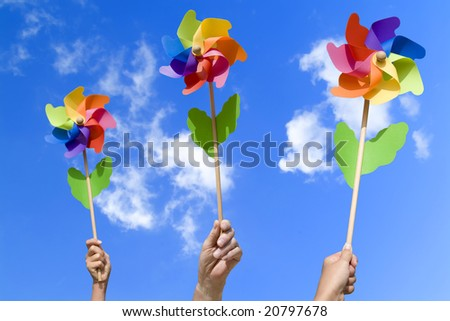 people with colorful small windmills in their hands, concept of wind energy (blue sky) - stock photo