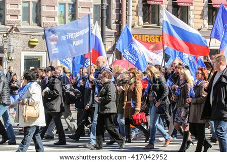 People with flags of the party and the country. St. Petersburg, Russia - 1 May, 2016. Day festive demonstration on the Nevsky Prospect in St. Petersburg, the first of May.