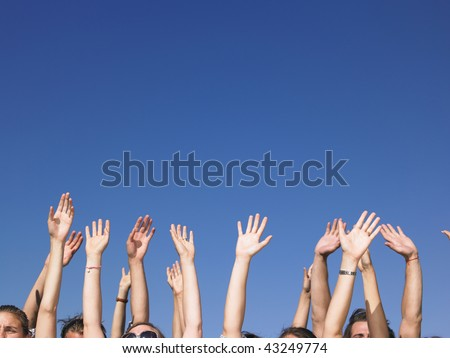People with hands in the air, with only the tops of their faces visible. Horizontal. - stock photo
