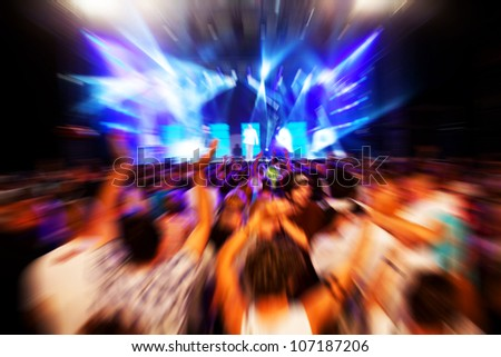 People with hands up having fun on a music concert / disco party. Dynamic motion. - stock photo