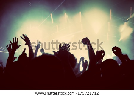 People with hands up having fun on a music concert, disco party. Vintage, retro style - stock photo