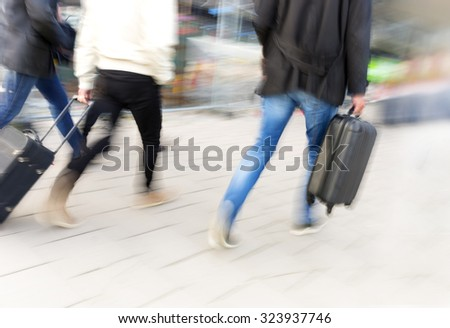 People with luggage in blurred motion to catch flight, train or ship. - stock photo
