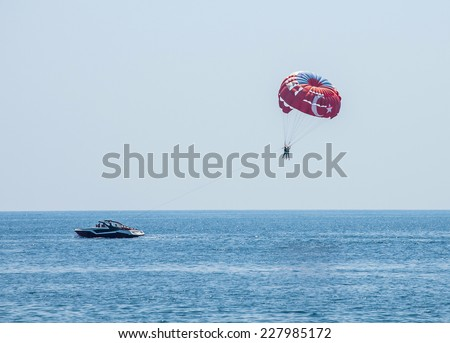People with parachute. Parasailing. (Parachute with Turkish flag pattern)  - stock photo