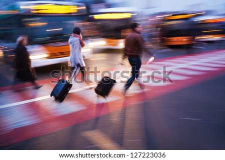 people with trolley bags crossing the street at a bus station