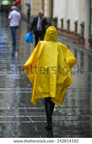people with umbrella walking in rain rush hour - stock photo
