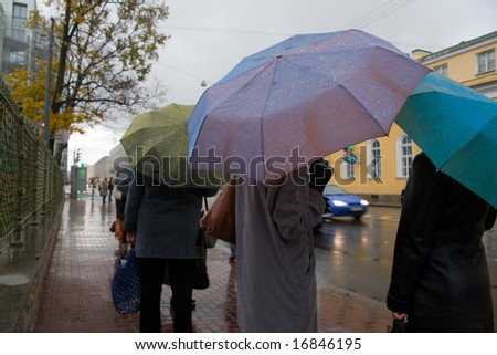 People with umbrellas expect public transport in rainy day