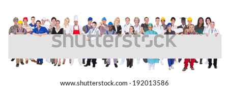 People with various occupations holding blank billboard against white background - stock photo