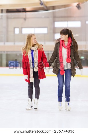people, women, friendship, sport and leisure concept - two happy girls friends on skating rink - stock photo