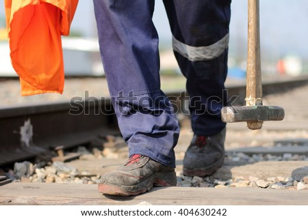 People working on the railroad with a sledge hammer and overalls in the hands
