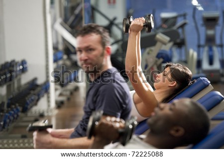 People working out with weights at health club - stock photo
