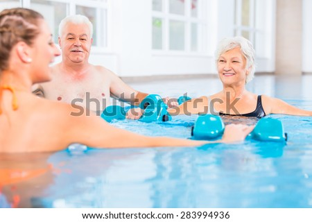 People young and senior in water gymnastics physiotherapy with dumbbells - stock photo