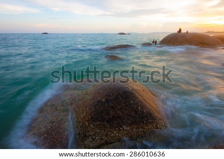 peoples in view of a rocky coast in sunset - stock photo