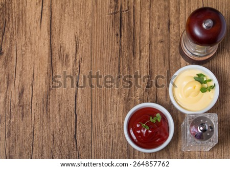 pepper and salt, ketchup and mayonnaise different kinds of sauces on wooden background top view - stock photo