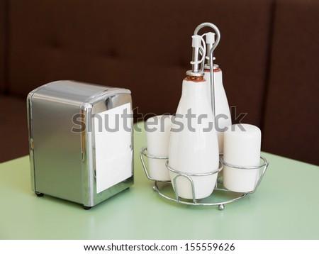 pepper and salt shakers, bottles for oil and vinegar, napkin holder - cafe table top set - stock photo