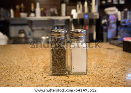 Pepper and Salt shakers sitting on a granite counter.