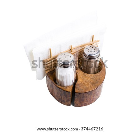 Pepper and salt shakers with napkin holder in rustic style on wooden board. Isolated on a white background. - stock photo