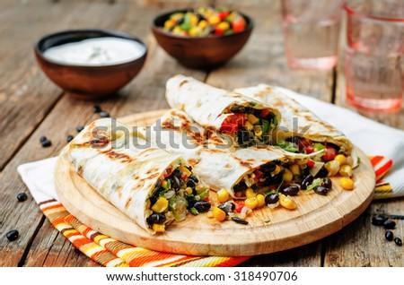 pepper corn black bean quinoa burritos on a dark wood background. the toning. selective focus - stock photo