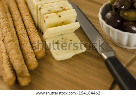 Pepper Jack cheese on a cutting board with some sesame seed bread sticks and a ramekin full of olives - stock photo