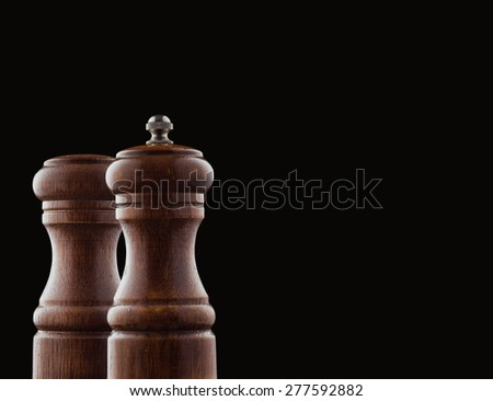 Pepper mill and salt isolated on black background with copy space - stock photo