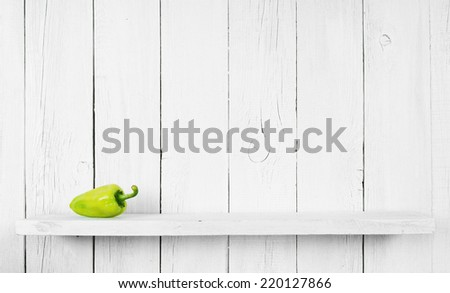 Pepper on a wooden shelf. On a wooden, white background. - stock photo