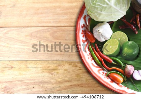 Pepper, onion, garlic and vegetables in a round tray on a wooden background top view.