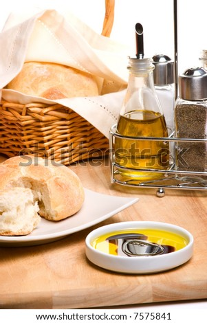Pepper pot with black pepper, fresh bread, bottle of olive oil and spicy herbs on wooden cut board - stock photo