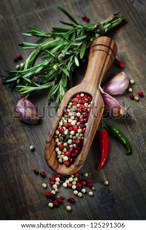 Peppercorn mix in wooden scoop, herbs and spices - stock photo