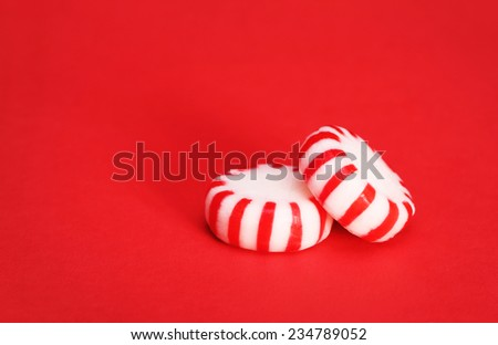 Peppermint Candy over Red Christmas background. Macro. - stock photo