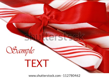 Peppermint candy sticks with red satin ribbon on white background with copy space.  Macro with shallow dof. - stock photo