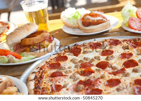 Pepperoni Pizza on Table with Food - stock photo
