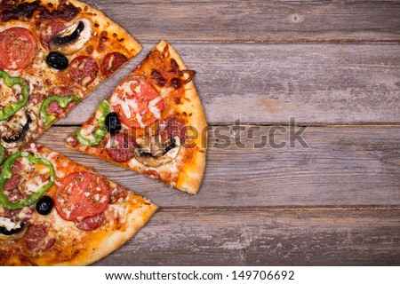Pepperoni pizza with sliced vegetables on rustic, vintage style wood background - stock photo