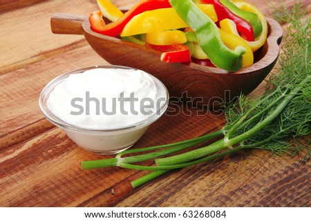peppers and sour cream over wooden tables - stock photo
