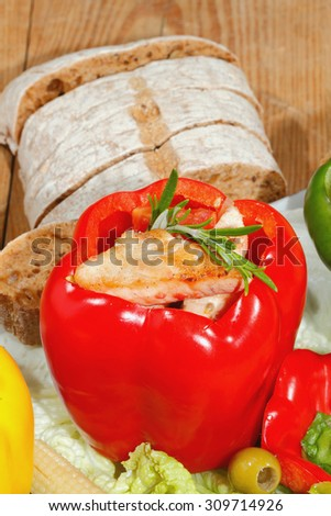 Peppers stuffed with grilled turkey breast and stewed tomatoes, zucchini and vegetables garnished with lettuce leaves, corn cobs, olives and rosemary - stock photo