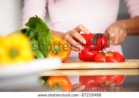 Peppers - woman cutting red pepper. Closeup of woman cutting red pepper making salad. - stock photo