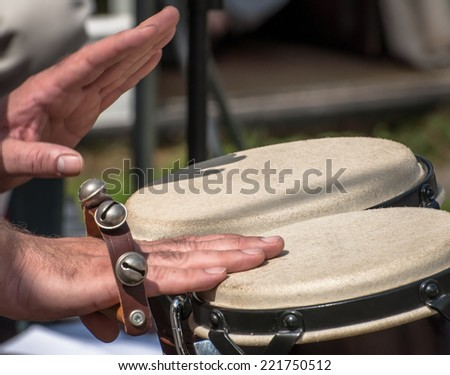 Percussionist playing with sleigh bells and bongos. - stock photo
