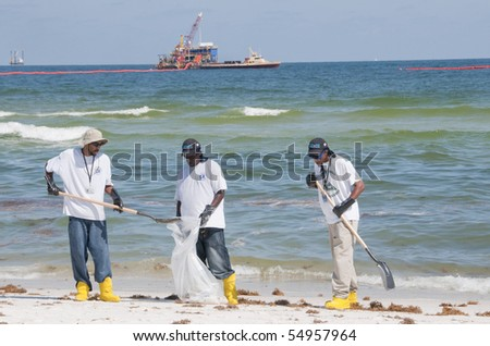 PERDIDO KEY, FL - JUNE 10: Oil spill workers collect tainted debris and dark oil patches along the beach as oil washes ashore on June 10, 2010 at Perdido Pass, AL. - stock photo